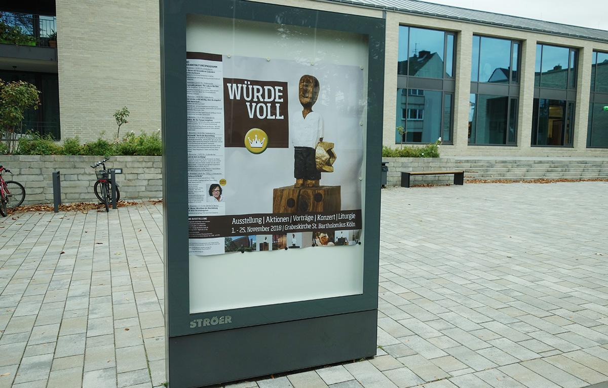 WürdeVoll – Ausstellung | Aktionen | Vorträge| Konzert| Liturgie vom 1. bis 25. November 2018 in Köln Bickendorf | Plakat vor dem BiOs-Inn und der Pfarrkirche St. Rochus.